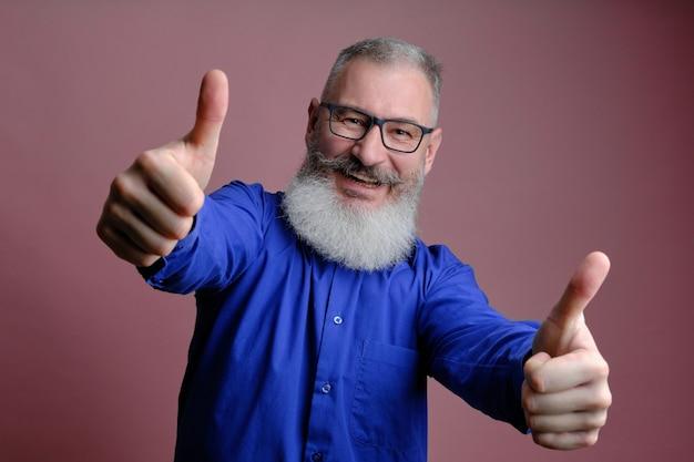Portret dojrzały brodaty mężczyzna ubrany w niebieską koszulę, wskazując kciuki do góry na różowej ścianie, kaukaski mężczyzna z brodą uśmiechnięty