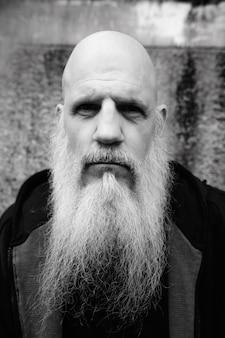 Portret dojrzały łysy mężczyzna z długą siwą brodą przed grunge betonową ścianą na zewnątrz w czerni i bieli