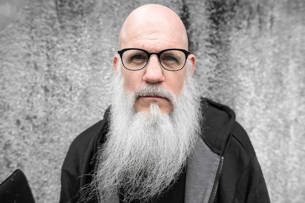 Portret dojrzały łysy mężczyzna z długą siwą brodą przed grunge betonową ścianą na zewnątrz