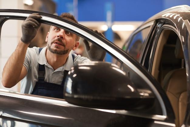 Portret dojrzały mechanik sprawdzający izolację okien luksusowego samochodu w warsztacie samochodowym, miejsce na kopię