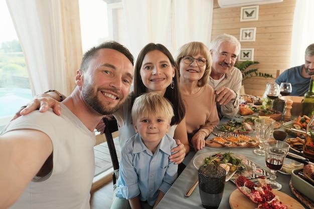 Portret dojrzały mężczyzna co selfie portret jego wielkiej rodziny, gdy siedzą przy stole podczas kolacji w domu