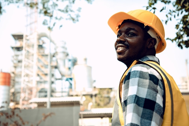 Portret dojrzały mężczyzna inżynier budowy uśmiechnięty pewny siebie z jasnym uśmiechem na kierownika budowy na sobie kask i kamizelkę odblaskową w ogrodzie. pozytywne myślenie