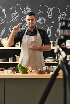 Portret dojrzały mężczyzna w fartuchu, wskazując na warzywo w dłoniach i opowiadając o przepisie