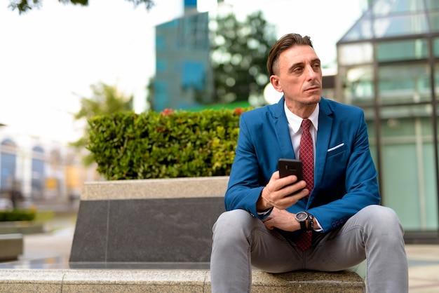 Portret dojrzały przystojny biznesmen włoski relaks na zewnątrz budynku