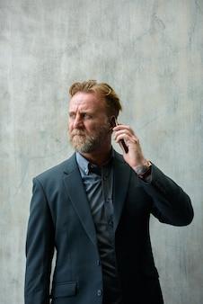 Portret dojrzały przystojny brodaty biznesmen o blond włosach w garniturze na betonowej ścianie na zewnątrz