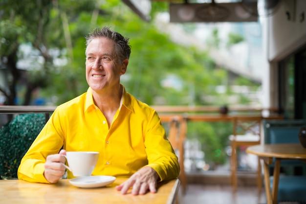 Portret dojrzały przystojny mężczyzna siedzi w kawiarni