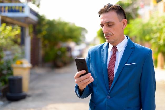 Portret dojrzały przystojny włoski biznesmen na ulicach na zewnątrz