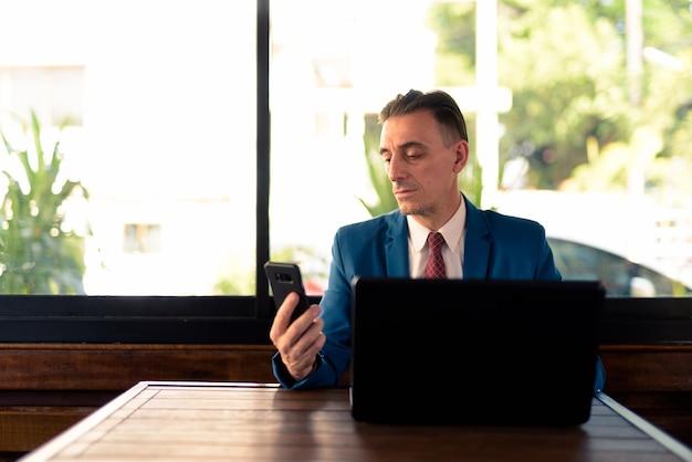 Portret dojrzały przystojny włoski biznesmen relaks w kawiarni