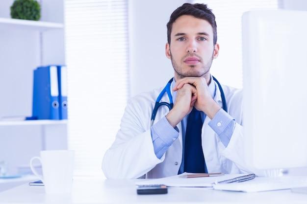 Portret doktorska patrzeje kamera z rękami składać