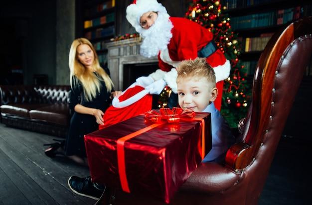 Portret domu rodzinnego. rodzice i syn wspólnie spędzają czas w czasie świąt bożego narodzenia