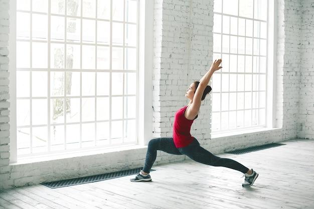 Portret dopasowanej młodej europejki w butach do biegania, praktykującej różne asany jogi w lekkiej, przestronnej sali gimnastycznej, wykonując pozę półksiężyca lub wysoki lonż. koncepcja energii, elastyczności, siły i mocy