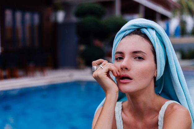 Portret dopasowanej szczupłej młodej kobiety rasy kaukaskiej w niebieskim bikini na zewnątrz willi przy basenie w deszczowy dzień