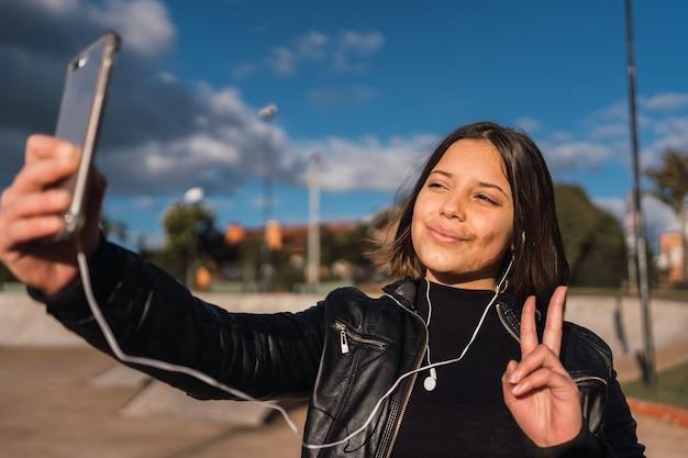 Portret dorastającej dziewczyny przy selfie co znak v.