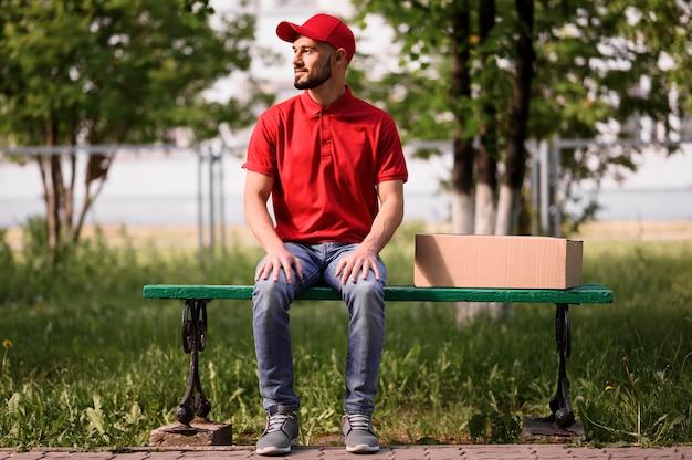 Portret doręczeniowego mężczyzna obsiadanie na ławce
