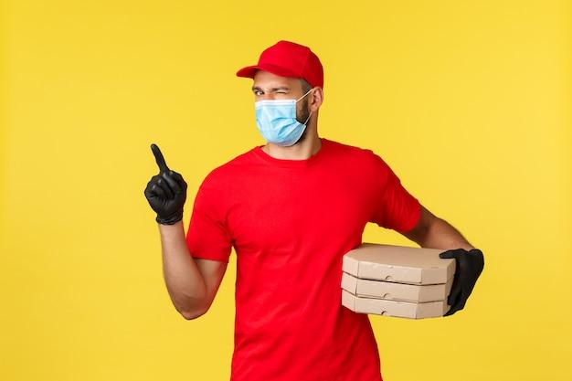 Portret doręczeniowy mężczyzna z twarzy maską i pizz pudełkami