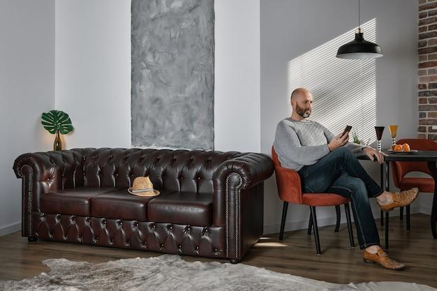 Portret dorosłego brodatego mężczyzny we wnętrzu salonu, utrzymany w stylu loftowym