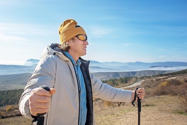 Portret dorosłego mężczyzny z kijami do nordic walking, stojącego wysoko w górach.