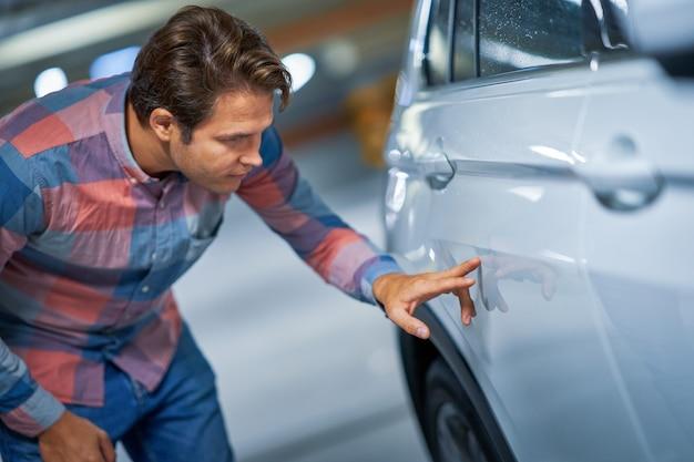 Portret dorosłego mężczyzny z porysowanym samochodem na podziemnym parkingu