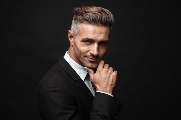 Portret dorosłego nieogolonego biznesmena ubranego w formalny garnitur, uśmiechającego się i patrzącego na kamerę na białym tle nad czarną ścianą