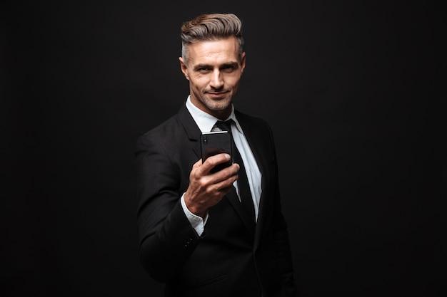 Portret dorosłego nieogolonego biznesmena ubranego w formalny garnitur, używającego telefonu komórkowego i patrzącego na kamerę na białym tle nad czarną ścianą