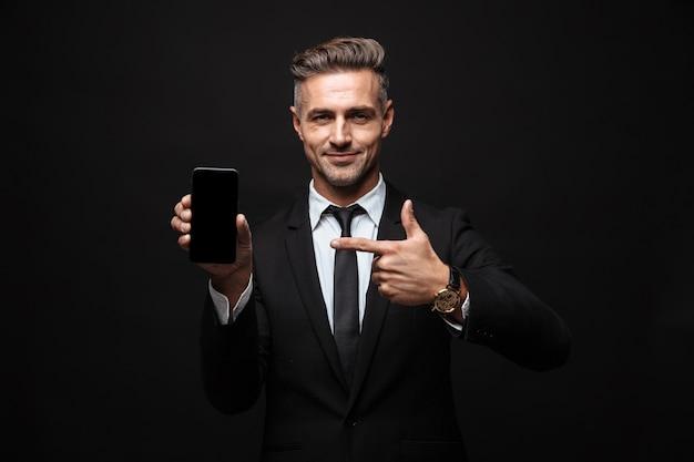 Portret dorosłego, pewnego siebie biznesmena ubranego w formalny garnitur, uśmiechającego się i wskazującego palcem na telefonie komórkowym na białym tle nad czarną ścianą