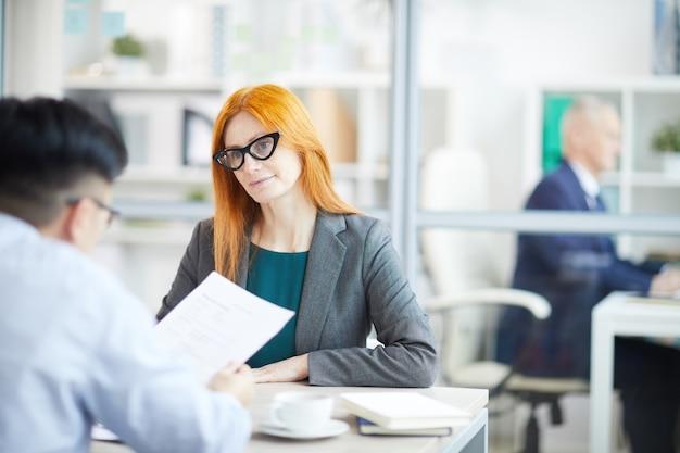 Portret dorosłego rudowłosy bizneswoman rozmawia z młodym człowiekiem o wolne miejsce pracy w biurze