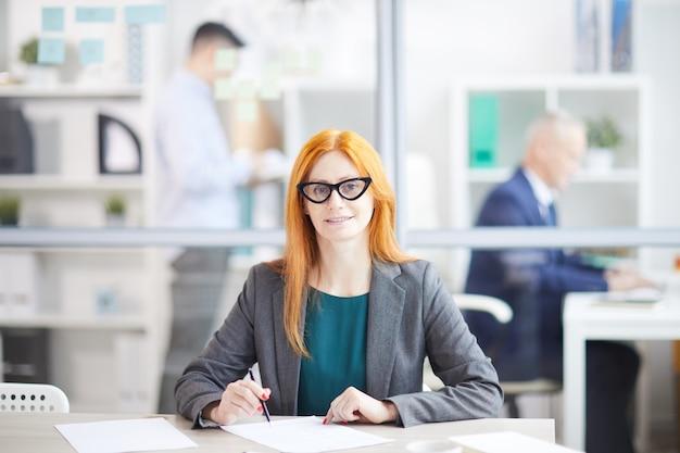 Portret dorosłego rudowłosy bizneswoman uśmiecha się, stwarzając w miejscu pracy w biurze