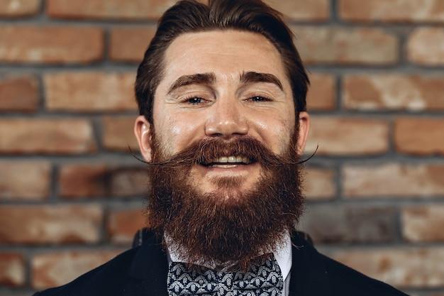 Portret dorosłego szczęśliwego człowieka z wąsami i brodą, pozowanie przed murem i uśmiechając się zębami. koncepcja wyrażenia