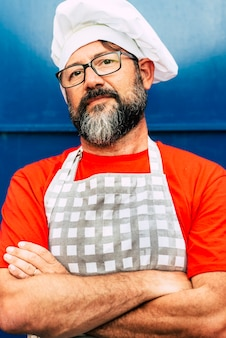 Portret dorosłego szefa kuchni hipster brodaty mężczyzna patrząc na kamery i nosić biały kapelusz koncepcja restauracji lub kawiarni i ludzi pracujących nad tym okulary i czerwony niebieski obraz kolory