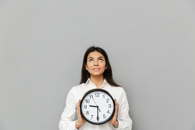 Portret dorosłej kobiety 30s ubrań biurowych, trzymając okrągły zegar i patrząc w górę na copyspace, odizolowane na szarej ścianie