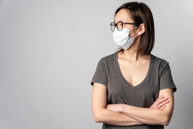 Portret dorosłej kobiety jest ubranym chirurgicznie maskę