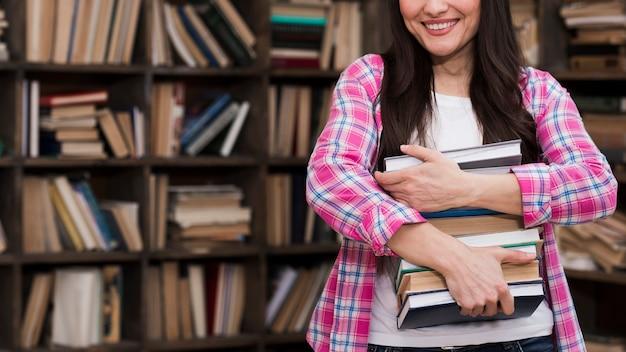 Portret dorosłej kobiety mienia stos książki