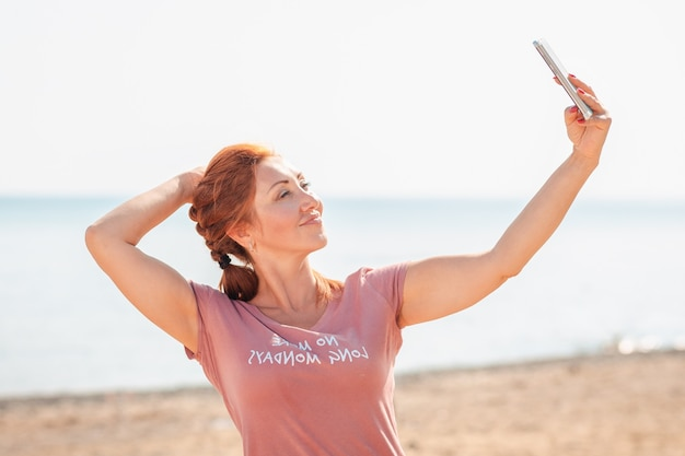 Portret dorosłej kobiety piękne pozowanie podczas robienia selfie na smartfonie.