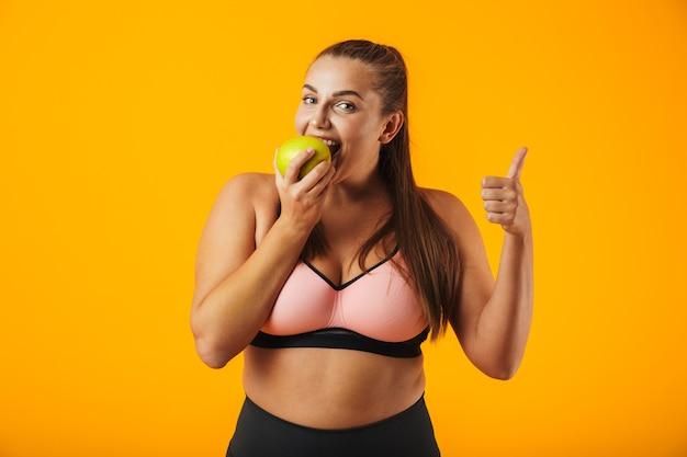 Portret dorosłej kobiety pulchne w sportowy stanik jedzenie jabłka, odizolowane na żółtym tle
