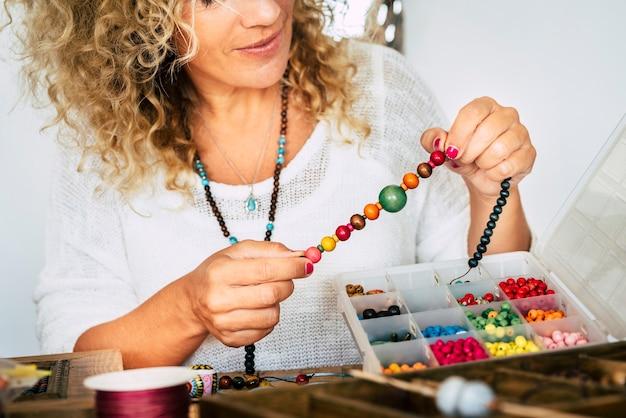 Portret dorosłej kobiety tworzącej bransoletki z koralików i naszyjnik w domu dla nowego, nowoczesnego i modnego biznesu