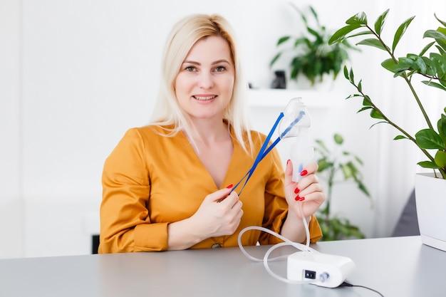 Portret dorosłej kobiety za pomocą nebulizatora parowego inhalatora wykonującego leczenie aerozolem inhalacyjnym w domu lub szpitalu gojenie się wirusa grypy i astmy oskrzeli