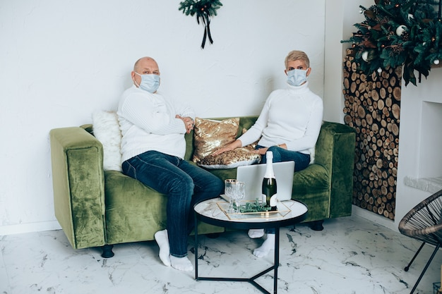 Portret dorosłej pary w maskach na twarzy na zielonej kanapie za pomocą laptopa z okazji świąt bożego narodzenia.