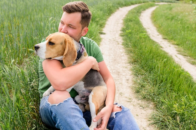 Portret dorosłej samiec trzyma ślicznego beagle