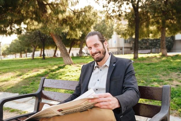 Portret dorosły przystojny mężczyzna w garniturze uśmiecha się do ciebie, siedząc na ławce w parku miejskim i czytając gazetę
