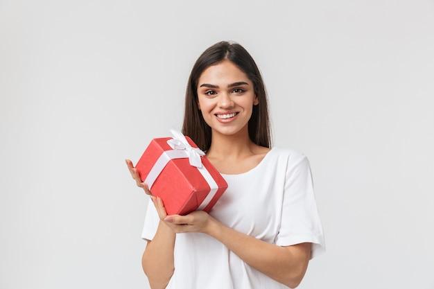 Portret dorywczo ubrana piękna młoda kobieta stojąca na białym tle, trzymając pudełko