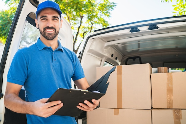 Portret dostawczego sprawdzającego produkty na liście kontrolnej, stojącego tuż obok swojej furgonetki. koncepcja dostawy i wysyłki.