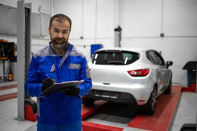 Portret doświadczonego, brodatego mechanika samochodowego w średnim wieku, stojącego w warsztacie samochodowym do obsługi i konserwacji.