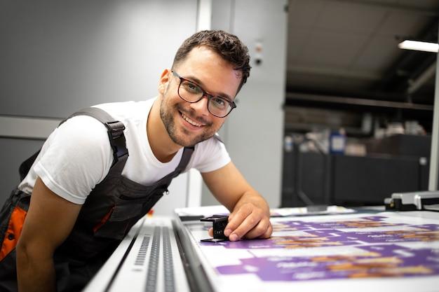 Portret doświadczonego drukarza kontrolującego jakość druku w nowoczesnej drukarni.