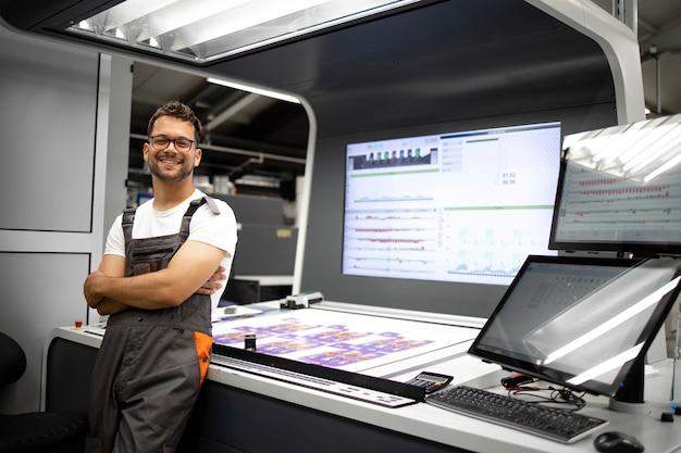 Portret doświadczonego drukarza stojącego przy stanowisku kontrolnym w nowoczesnej drukarni.