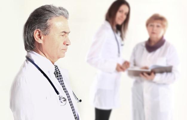 Portret doświadczonego lekarza na tle pracowników centrum medycznego.