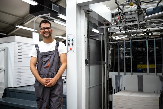 Portret doświadczonego typografa stojącego przy nowoczesnej maszynie drukarskiej w drukarni.