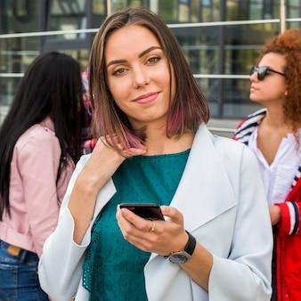 Portret dosyć elegancka kobiety mienia telefon komórkowy patrzeje kamerę