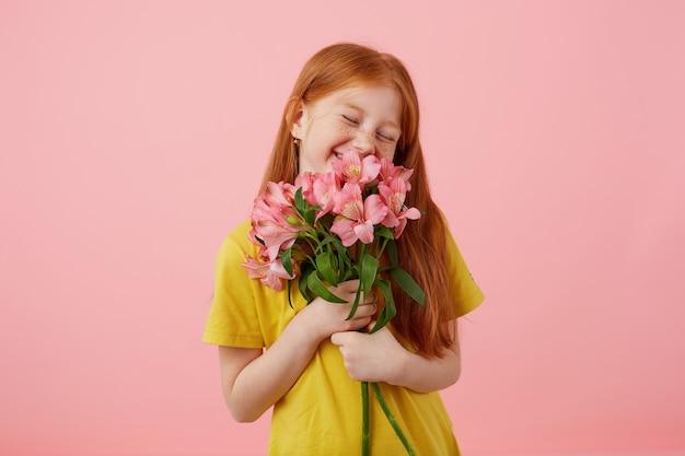 Portret drobna uśmiecha się piegi rudowłosa dziewczyna z dwoma ogonami, wygląda uroczo, nosi żółtą koszulkę, trzyma bukiet i stoi na różowym tle, rozkoszując się zapachem kwiatów.