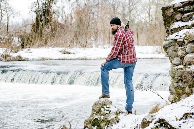 Portret drwal z siekierą na tle rzeki na wiosnę