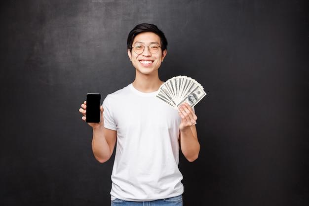 Portret dumnego bogatego młodego człowieka pokazującego dolary, fana pieniędzy i wyświetlacza telefonu komórkowego, uśmiechającego się, chwalącego się, gdzie wygrał, otrzymuje nagrodę pieniężną, stojącego zadowolonego na czarnej ścianie